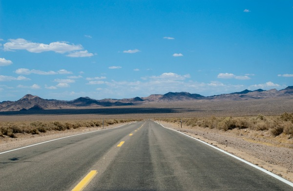 a long straight desert road disappears into the distance